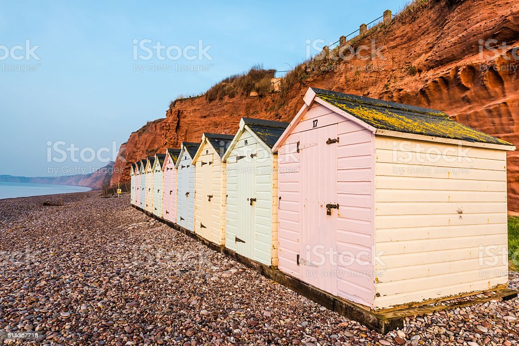 Beach hut row in pastel colors, red rock cliff background stock photo