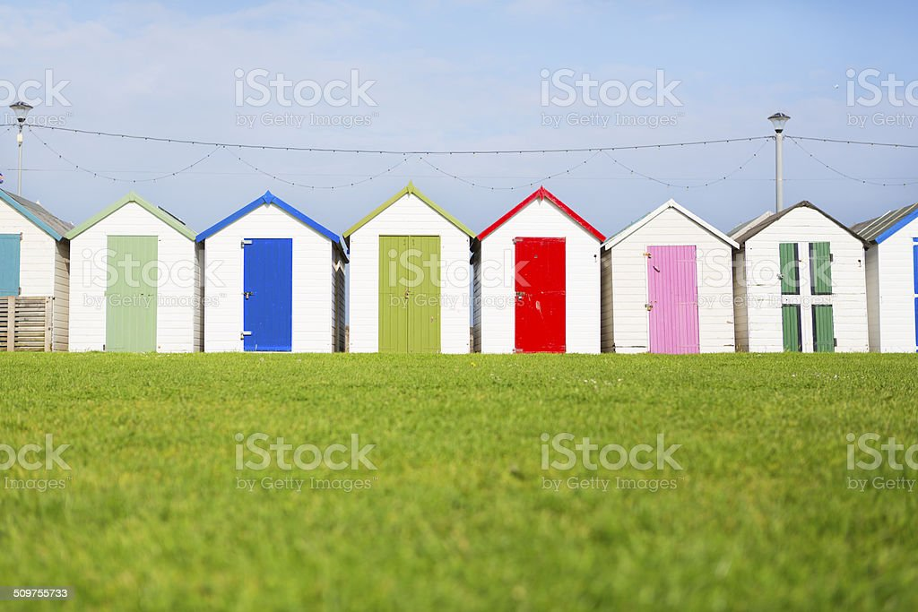 Beach Huts at Paignton The colourful beach huts of Paignton waterside. The photograph was taken at a low angle capturing foreground grass, and showing the huts at a square on angle. Beach Stock Photo