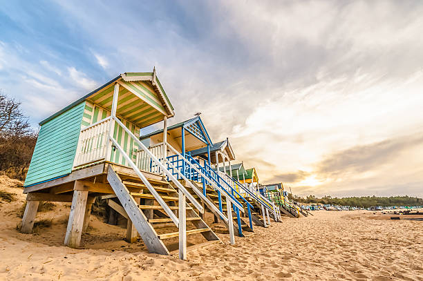 beach huts Long line of colorful beach huts at sunset. beach hut stock pictures, royalty-free photos & images