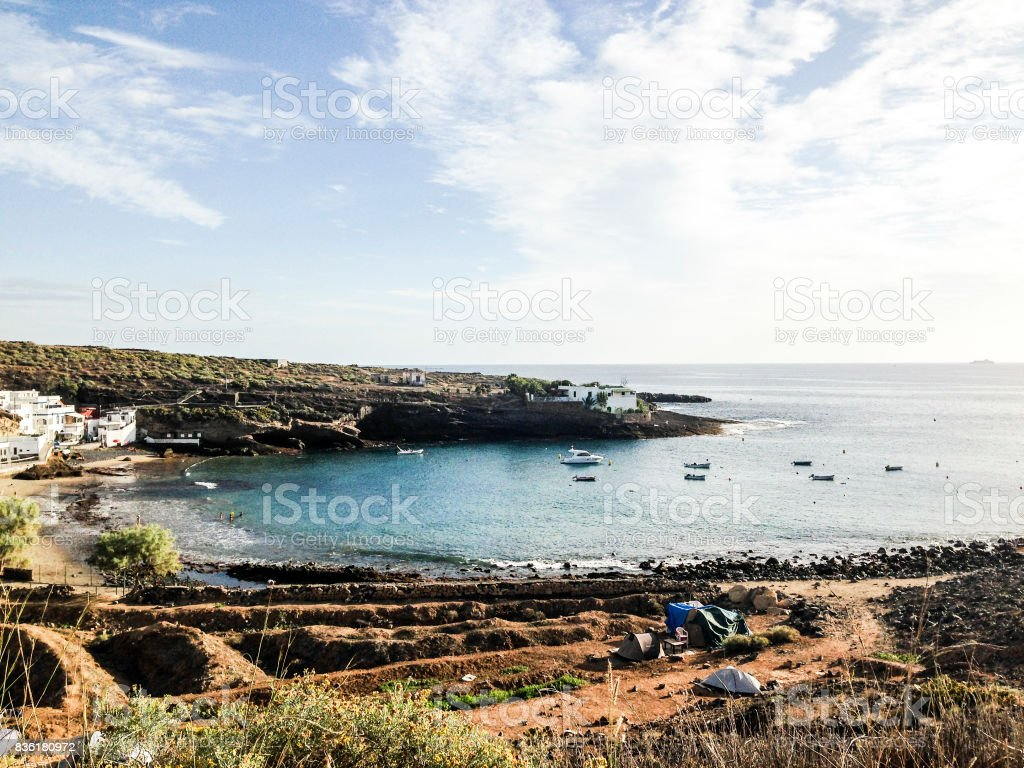 Beach in a bay with tents and boats. El Puertito, Tenerife. stock photo
