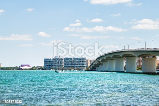 istock Beach in city of Sarasota, Florida on sunny day with cityscape and bay buildings by John Ringling causeway bridge in summer 1308874030