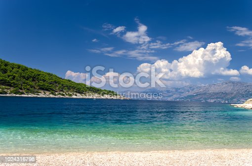 A clean, pebble beach on the Croatian coast near the small town of Pucisca, on the island of Brac. Dalmatian region, Adriatic Sea. Blue and turquoise water in the sea bay, coastline and high mountains in the background. Blue sky and white clouds. A typical picture for Croatia. Summer travel destinantion.