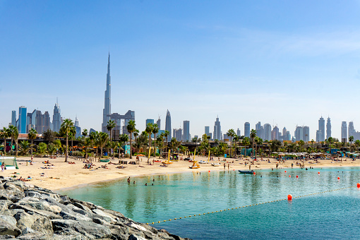 Beach in Dubai with people and skyscapers in the background on a sunny day
