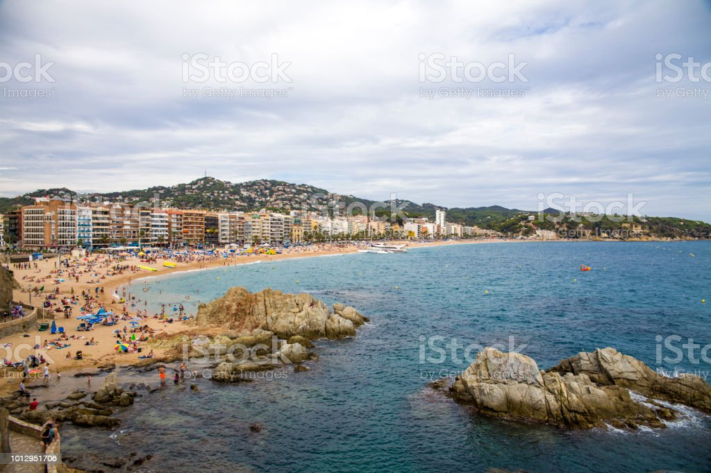 Beach in the city of Lloret de Mar on the Costa Brava. A beautiful beach in a holiday village in Spain. Buildings and hotels by the beach. – zdjęcie