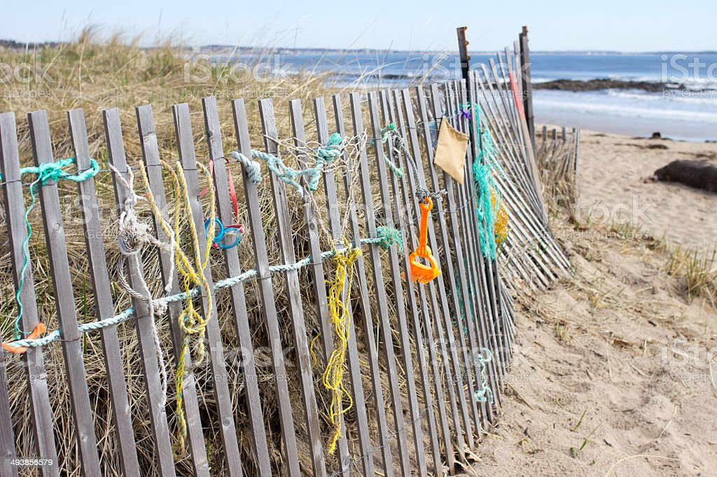 Beach items hanging on wooden fence near ocean stock photo