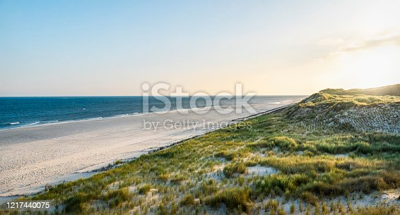 Summer scenery with empty beach, grassy dunes and North sea, on Sylt island, Germany. Summer vacation location on german island.