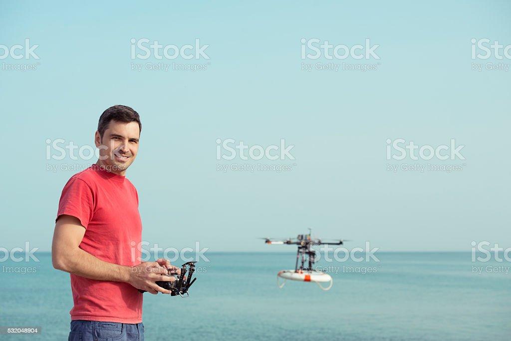 Beach lifeguard man piloting rescue drone. stock photo