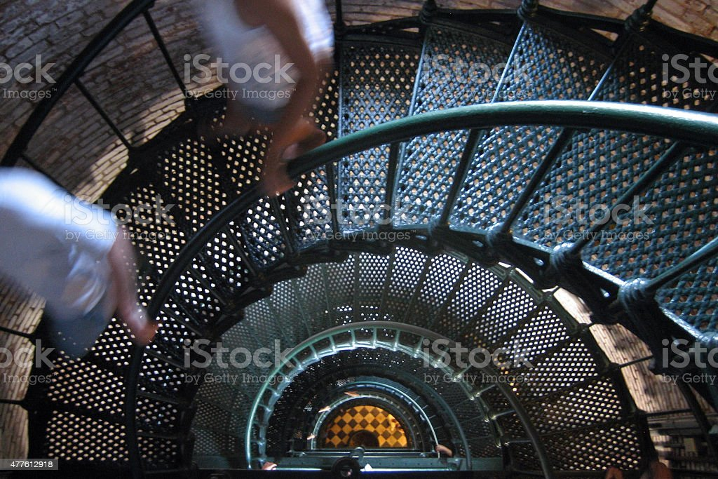 Beach lighthouse staircase with people descending stock photo