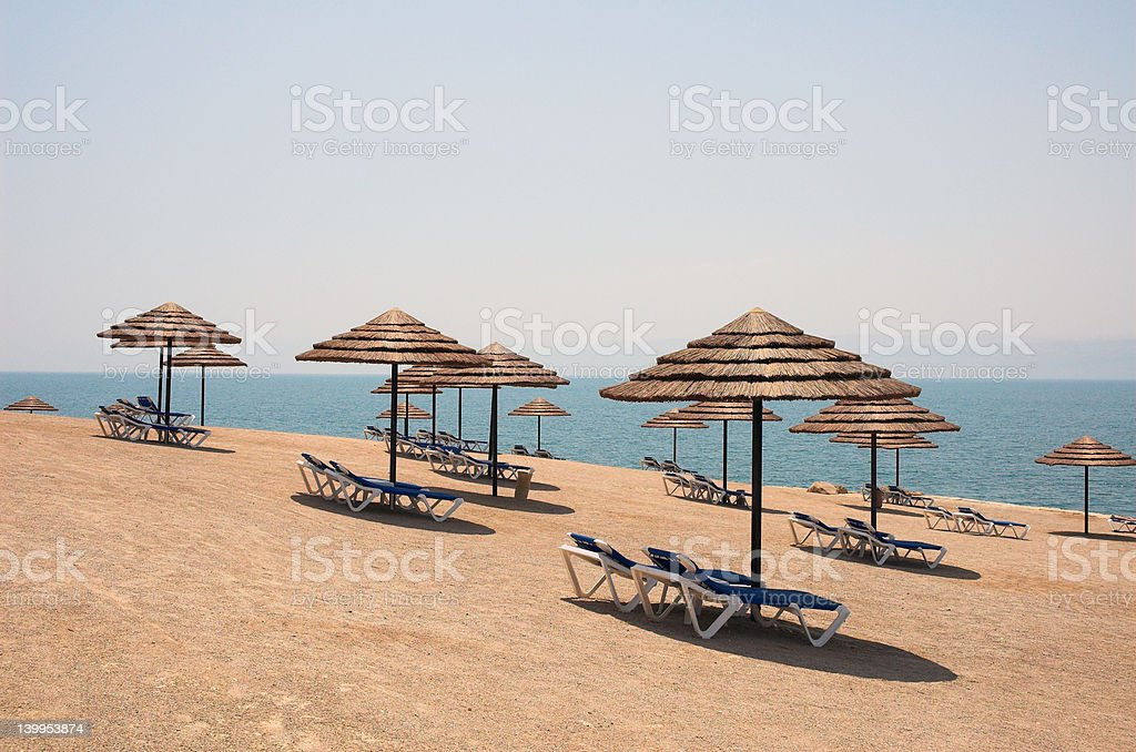 Beach, lounge chairs and umbrellas stock photo