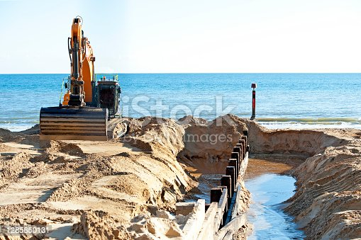 Contractors replace groynes during a time of  empty beach huts and beaches, as golden colours, winter sunlight and muted grey weather announce the onset of winter in Dorset during November