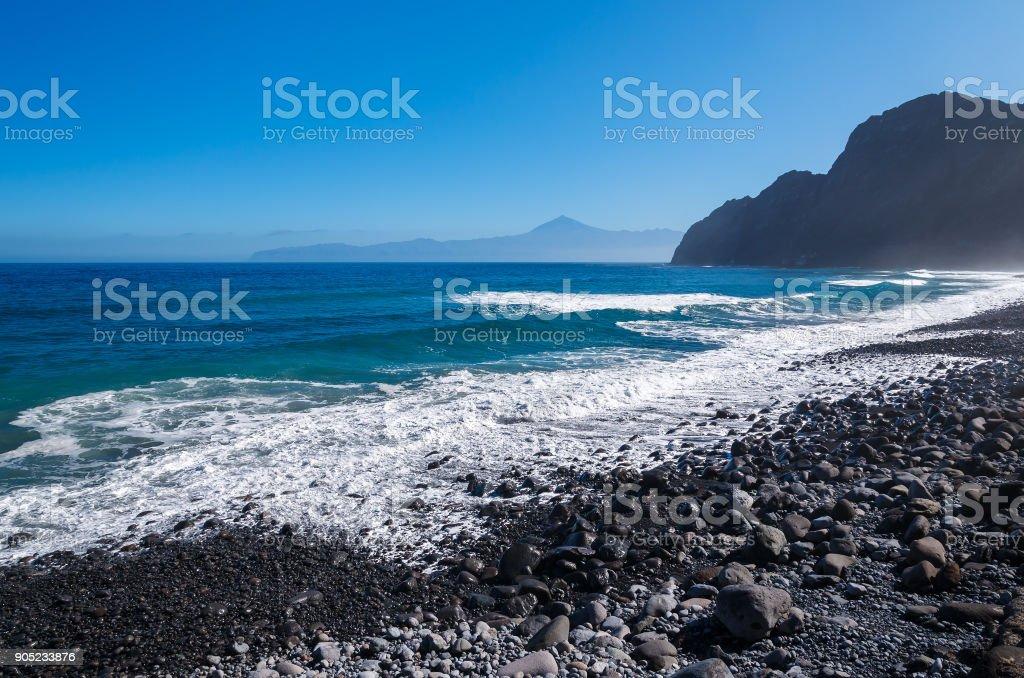 Beach ocean stones mountain Tenerife Teide volcano background, Santa Catalina, La Gomera, Canary Islands stock photo