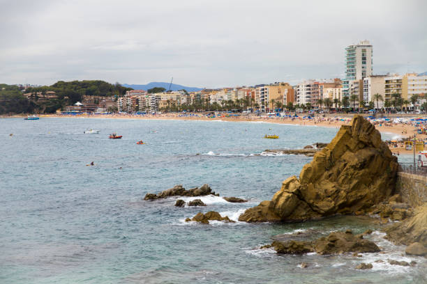Lloret de Mar / Spain - June 27, 2018: Beach off the coast of Lloret de Mar, Costa Brava. People on the beach lie on sun loungers under umbrellas. Resting under a castle on the beach in the city. – zdjęcie