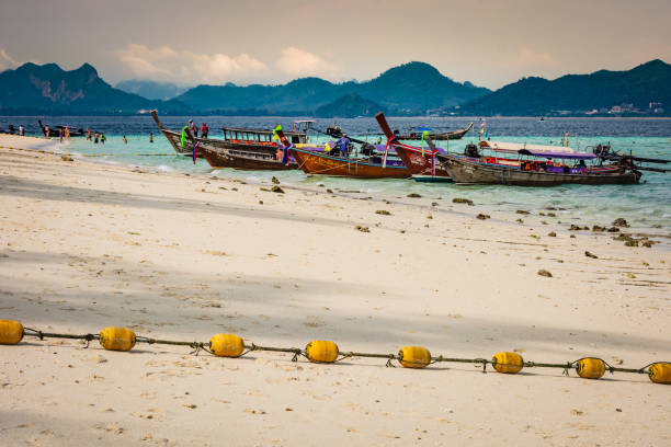 Beach on the island near Krabi, wooden boats and yellow buoys on the beach, the mountainous part of the island in the background – zdjęcie