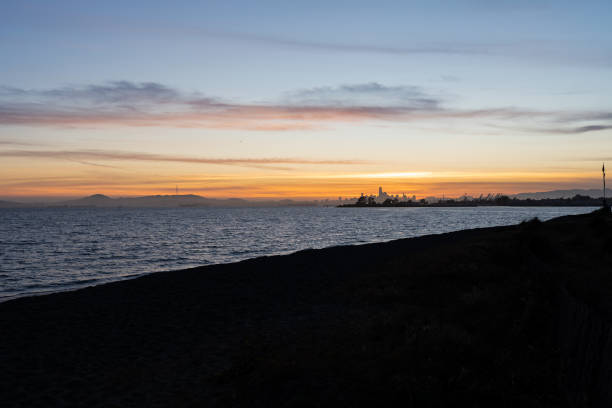 Beach overlooking San Francisco Bay Sunset at the Robert W. Crown Memorial State Beach in Alameda, California. City of San Francisco seen in the distance. alameda california stock pictures, royalty-free photos & images