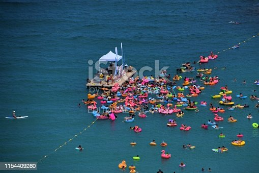 Menton, France - July 21 2018: Young people having fun in the middle of the sea at a floating beach party with DJ on platform. Summer holiday.