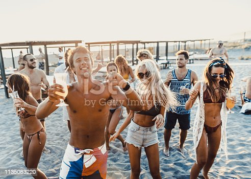 Large group of happy adults having fun while dancing on a party at the beach.