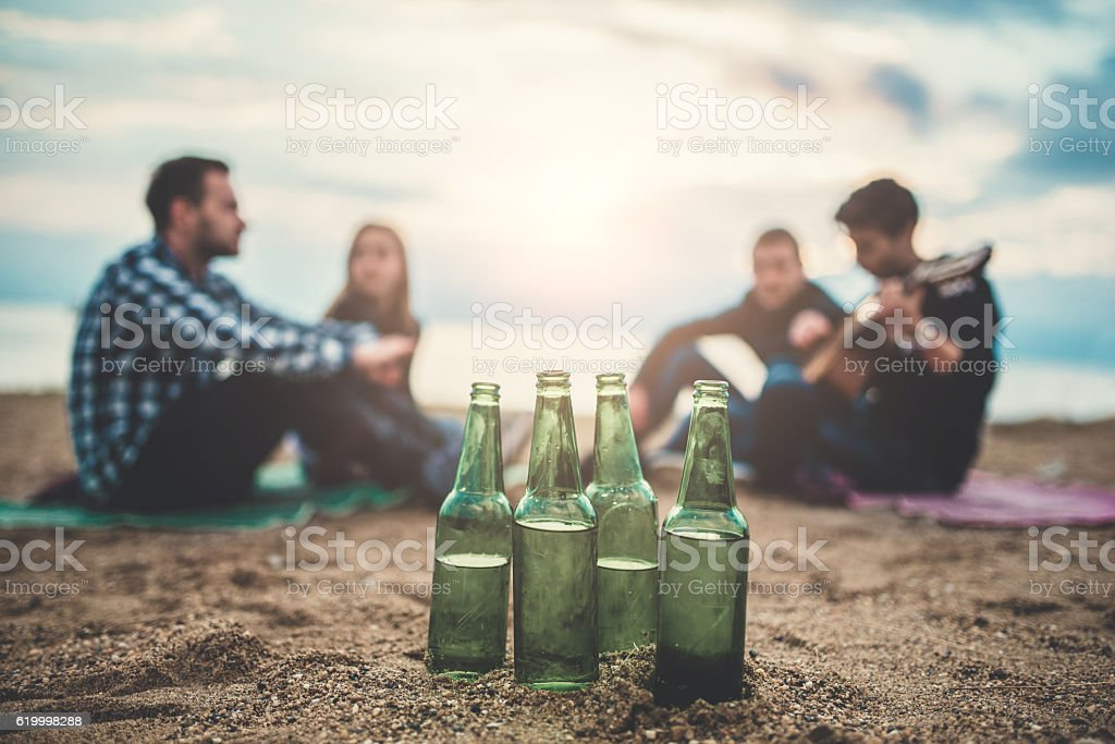 Beach Party with Beer Bottles and Friends with Guitar stock photo