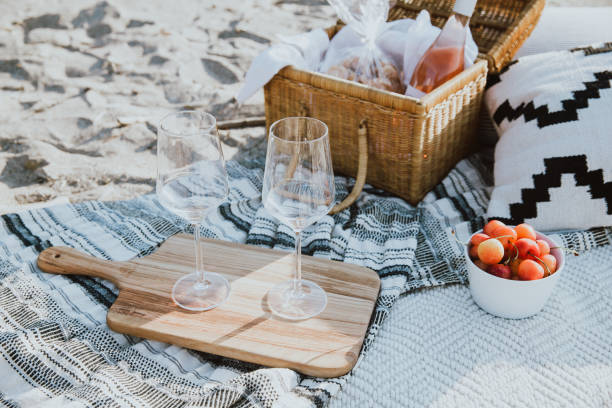 Beach Picnic Spread with Wine Glasses and Basket stock photo