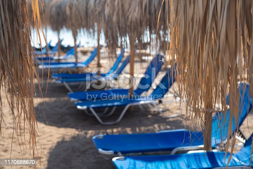 Sunbed and parasol of straw on the beach in Greece