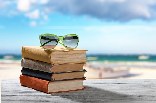 Books and sunglasses  on  beach background