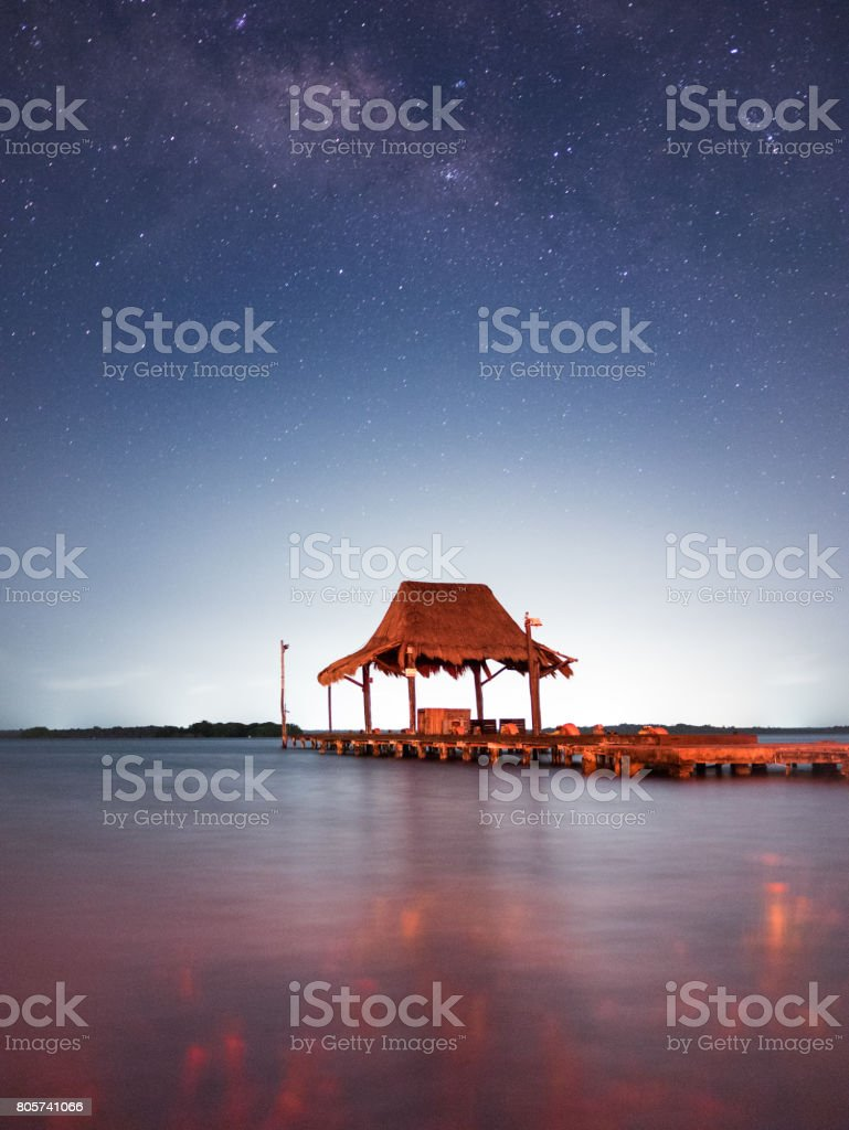 A pier in the waters in a clear night under a sky full of stars and...