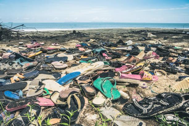 strand verschmutzung verworfen kunststoff flip flop müll - salzwasser sandalen stock-fotos und bilder