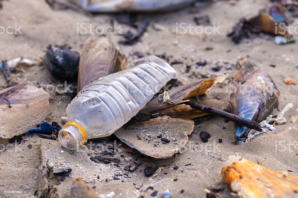 Beach pollution. Plastic bottles and other trash on sea beach royalty-free stock photo