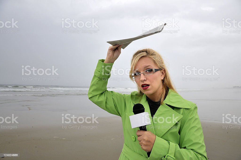 Beach Reporter Holding Newspaper Over Head stock photo