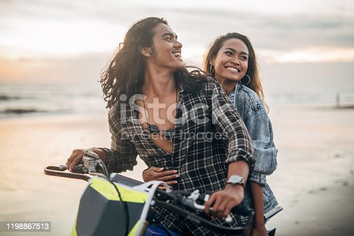 Young woman andyoung man sitting on motorbike at the beach