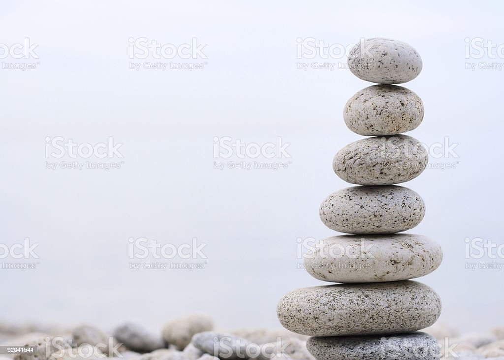 Beach rocks balancing on one another in an off center shot stock photo