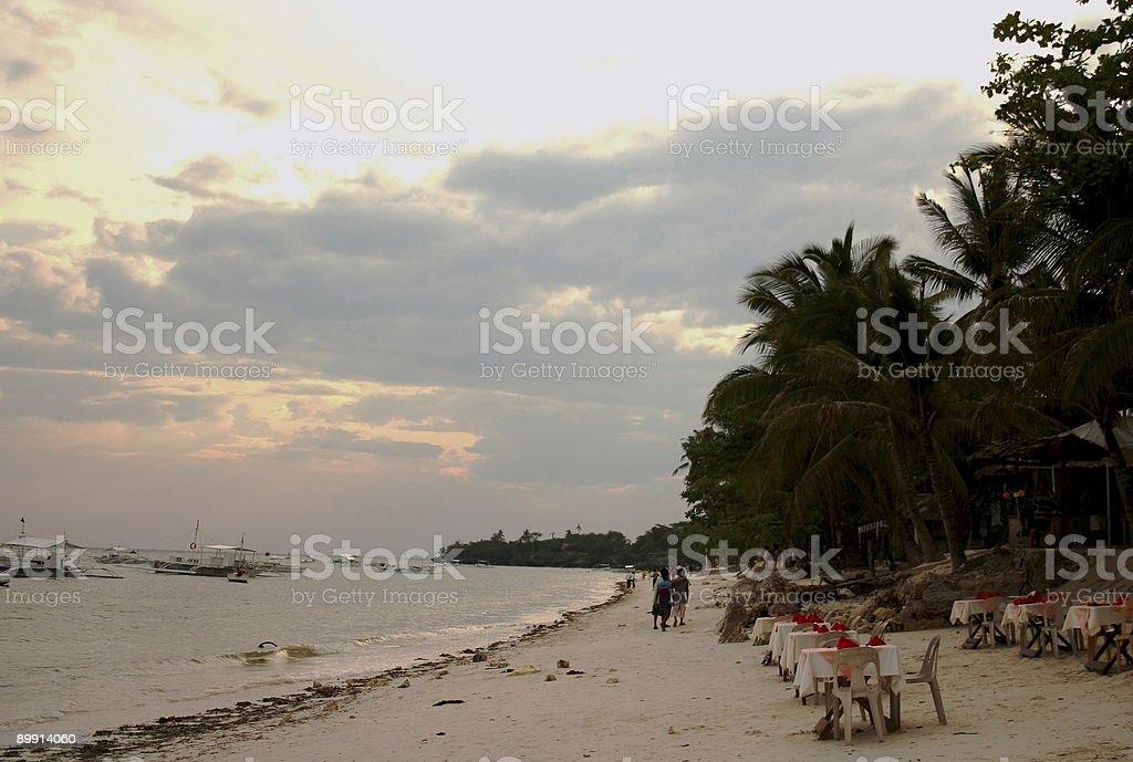 Cena de praia ao pôr do sol foto de stock royalty-free