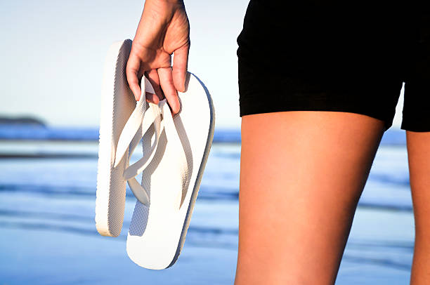 Beach Scene: Carrying Flip-Flops A woman on the beach, facing the sea with a pair of white sandles. hot sexy butts stock pictures, royalty-free photos & images