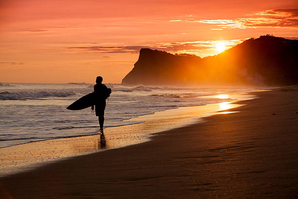 Beach scene in Nicaragua with surfer silhoette at sunset stock photo