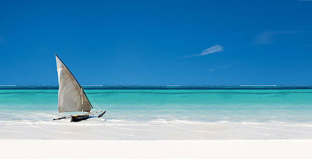 Beach scene Sail boat in the sea beside the beach with clear blue sky and white sand indo pacific ocean stock pictures, royalty-free photos & images
