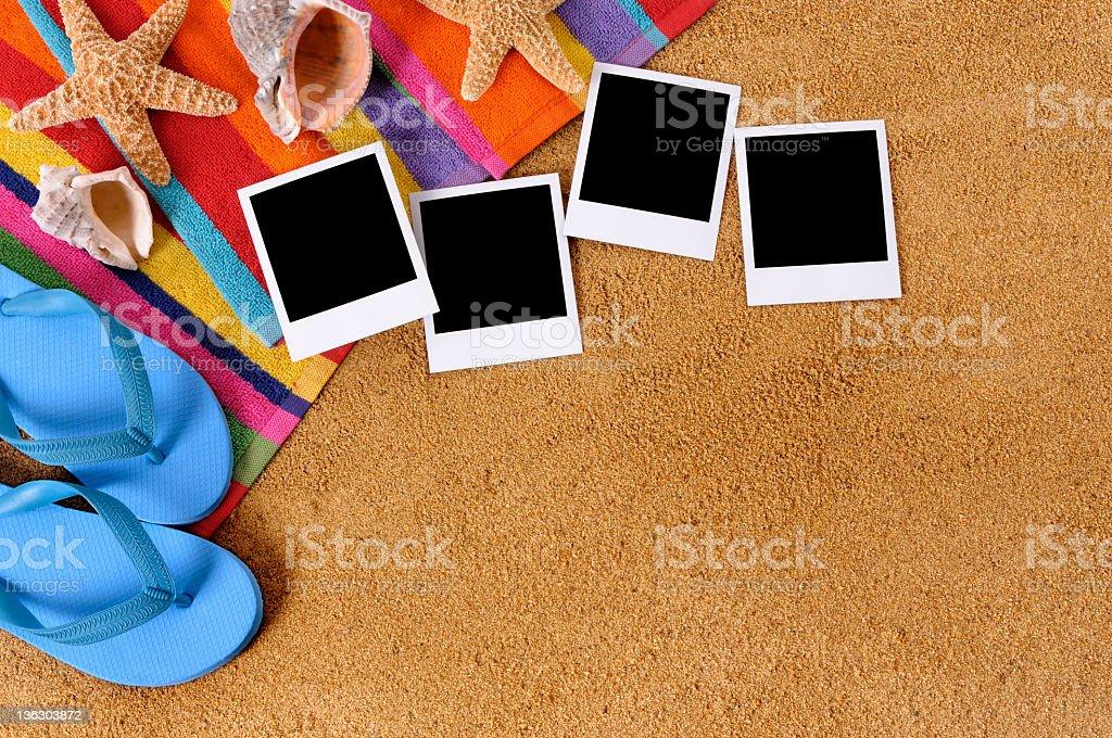 Beach scene with blank photo prints, towel, flip flops and starfish ....