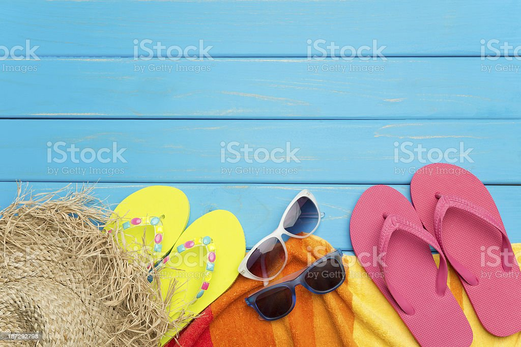 Beach scene with hat, thongs and blue wood decking stock photo