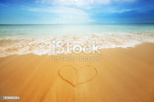 istock Beach scene with heart in the sand 180866084