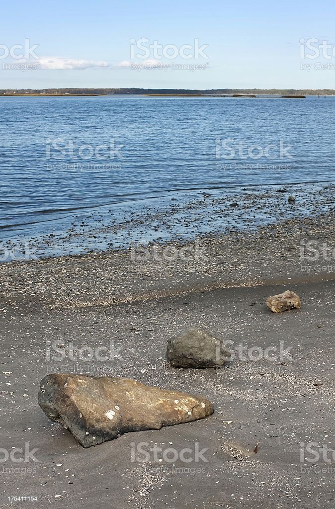 Beach scene with three stones along the shore stock photo