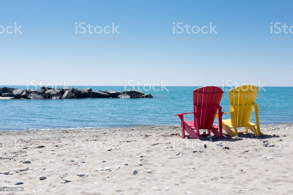 beach scene with two colorful adirondack chairs stock photo