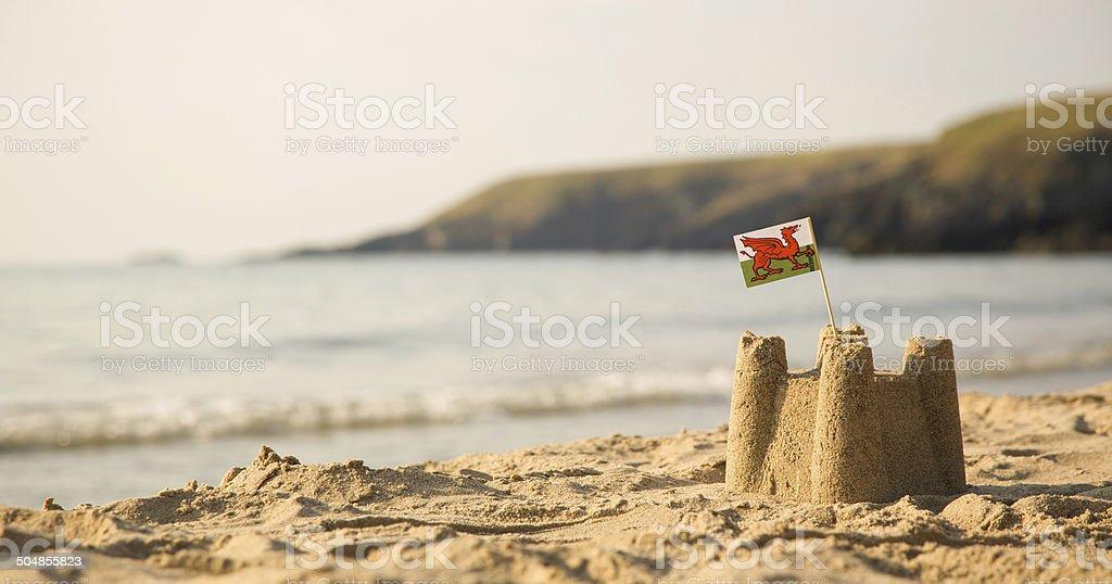 Beach, sea, sandcastle and  Welsh Flag stock photo