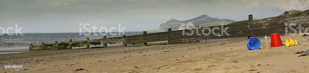 Beach, sea with buckets  sandcastle and windmill flag royalty-free stock photo