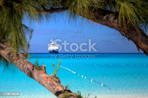 A ship waits on the horizon on a beautiful beach in the Caribbean.