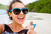 Beautiful young multicultural woman taking a selfie at the beach with her father photobombing in the background.