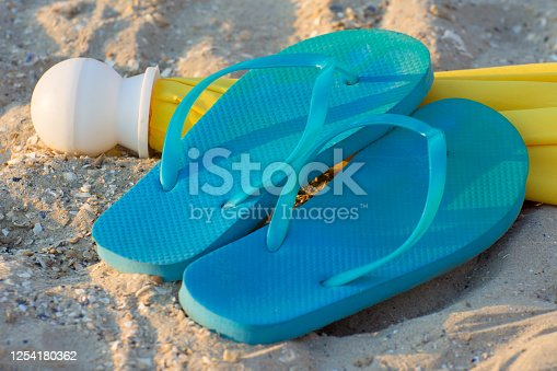 955947208 istock photo Beach slippers and a yellow umbrella on the sand. Holidays on the coast. 1254180362