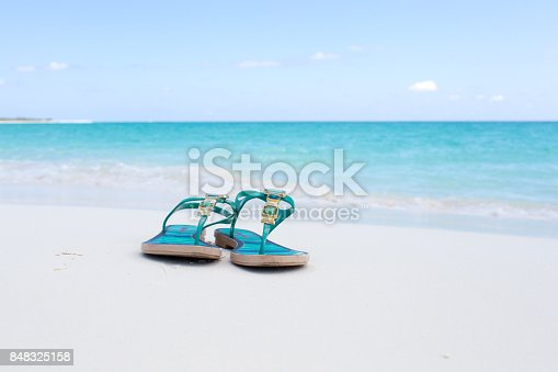 istock beach slippers on white sand 848325158