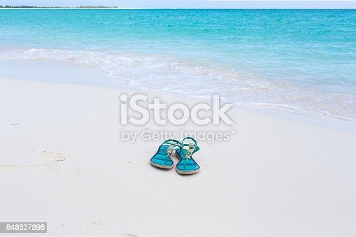 istock beach slippers on white sand 848327898