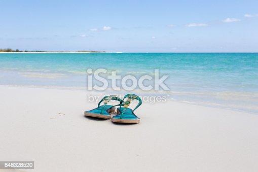 istock beach slippers on white sand 848328520