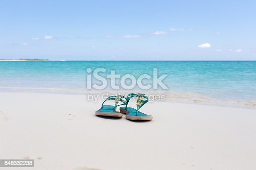 istock beach slippers on white sand 848332238