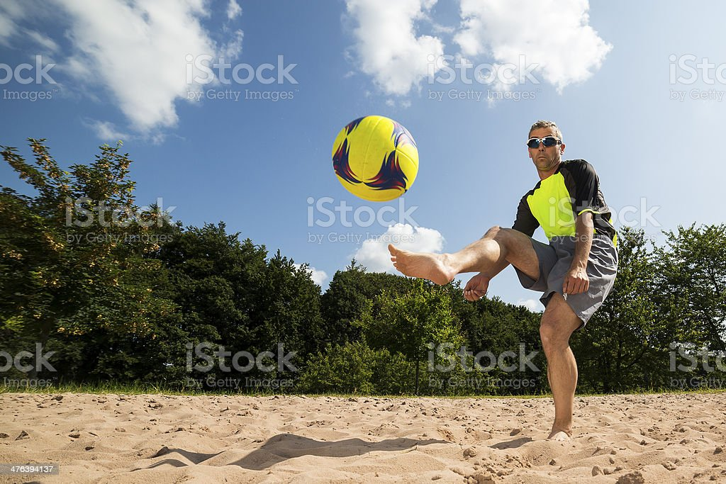 beach soccer player in a kick stock photo