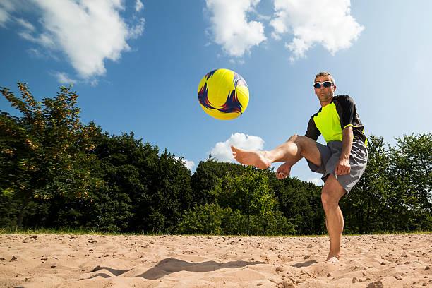jogador de futebol de praia em um chute - futebol de areia - fotografias e filmes do acervo